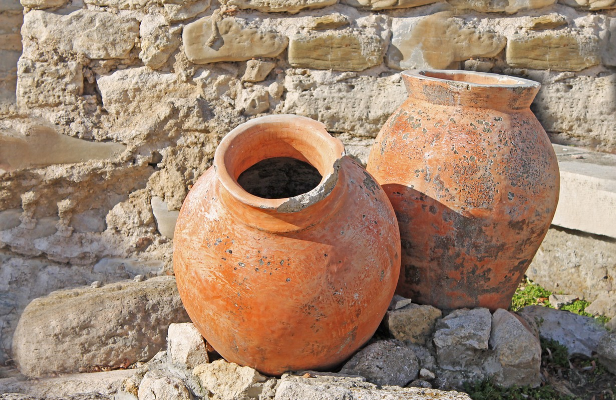 Two antique amphoras on the background of the ruins