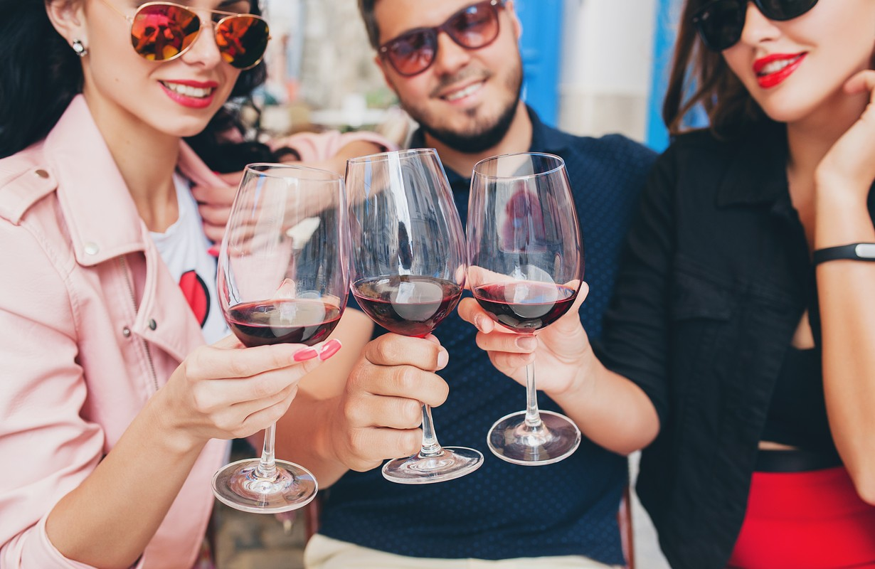 View Preview    young hipster company of friends sitting in city street cafe, holding glasses, toasting, celebrating, drinking wine, sunglasses, summer vacation, party, having fun, smiling, happy, positive