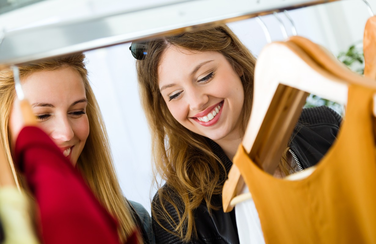 Portrait of two beautiful young women shopping in a clothes shop.