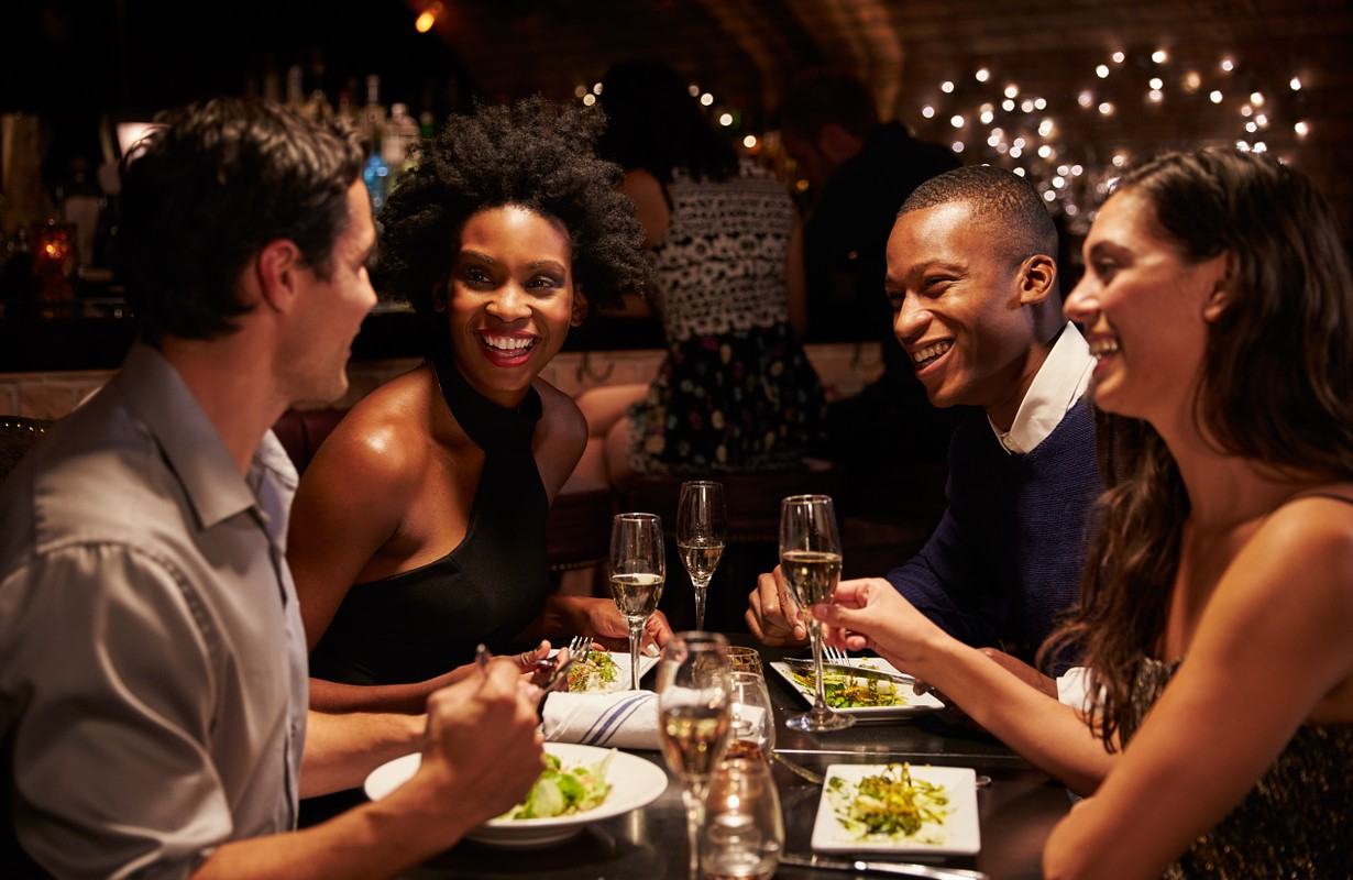 Two couples enjoying meal in restaurant together - Atlanta, Georgia