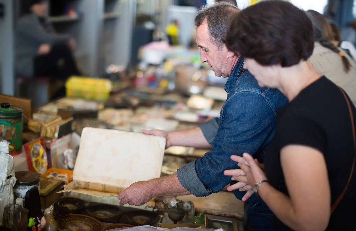 Positive couple of tourists study the range of flea market