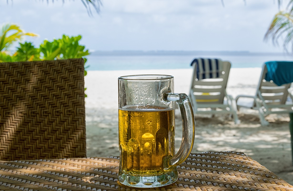 Ice cold beer mug with dew on the table in shadows in front of white sand beach