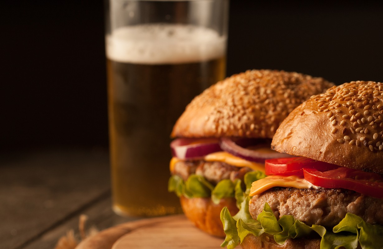 Home made hamburger with beef, onion, tomato, lettuce and cheese. Fresh burger close up on wooden rustic table with potato fries, beer and chips. Cheeseburger.