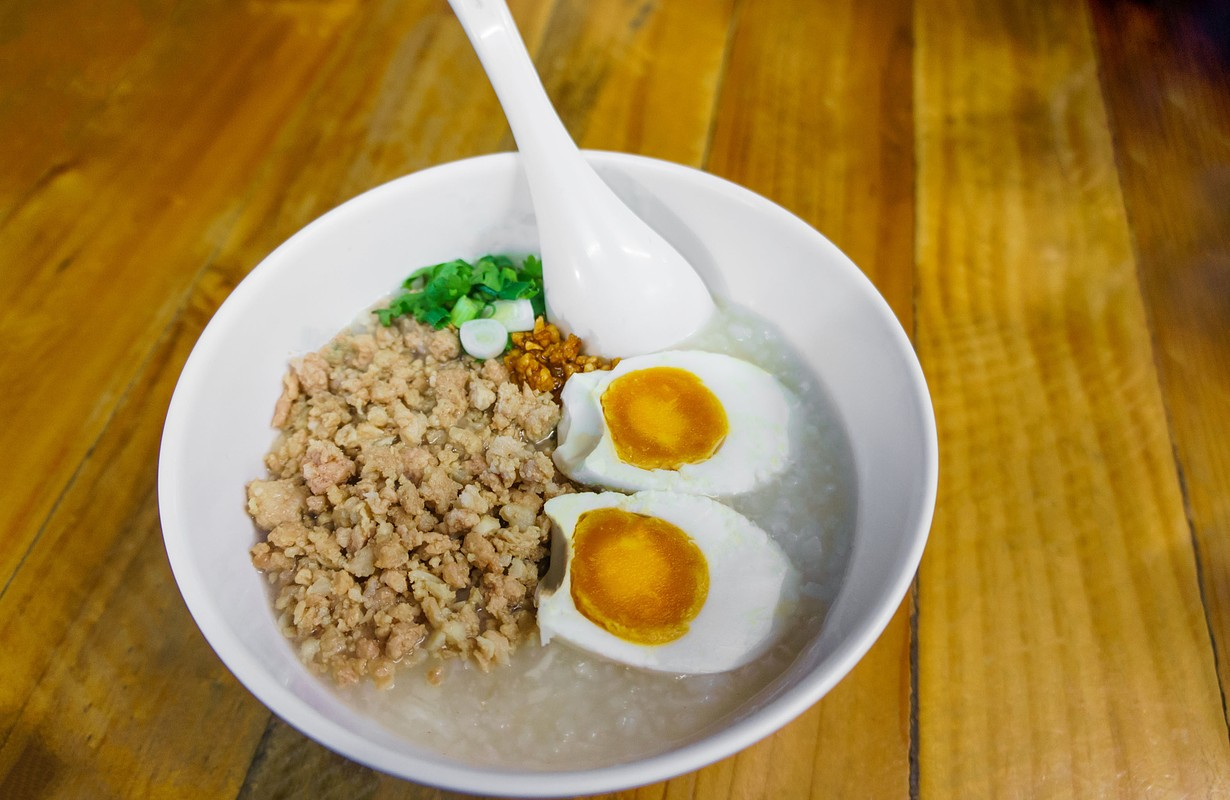 Minced pork congee with egg, fresh ginger and coriander on white cup and spoon over the wood table. Second view.