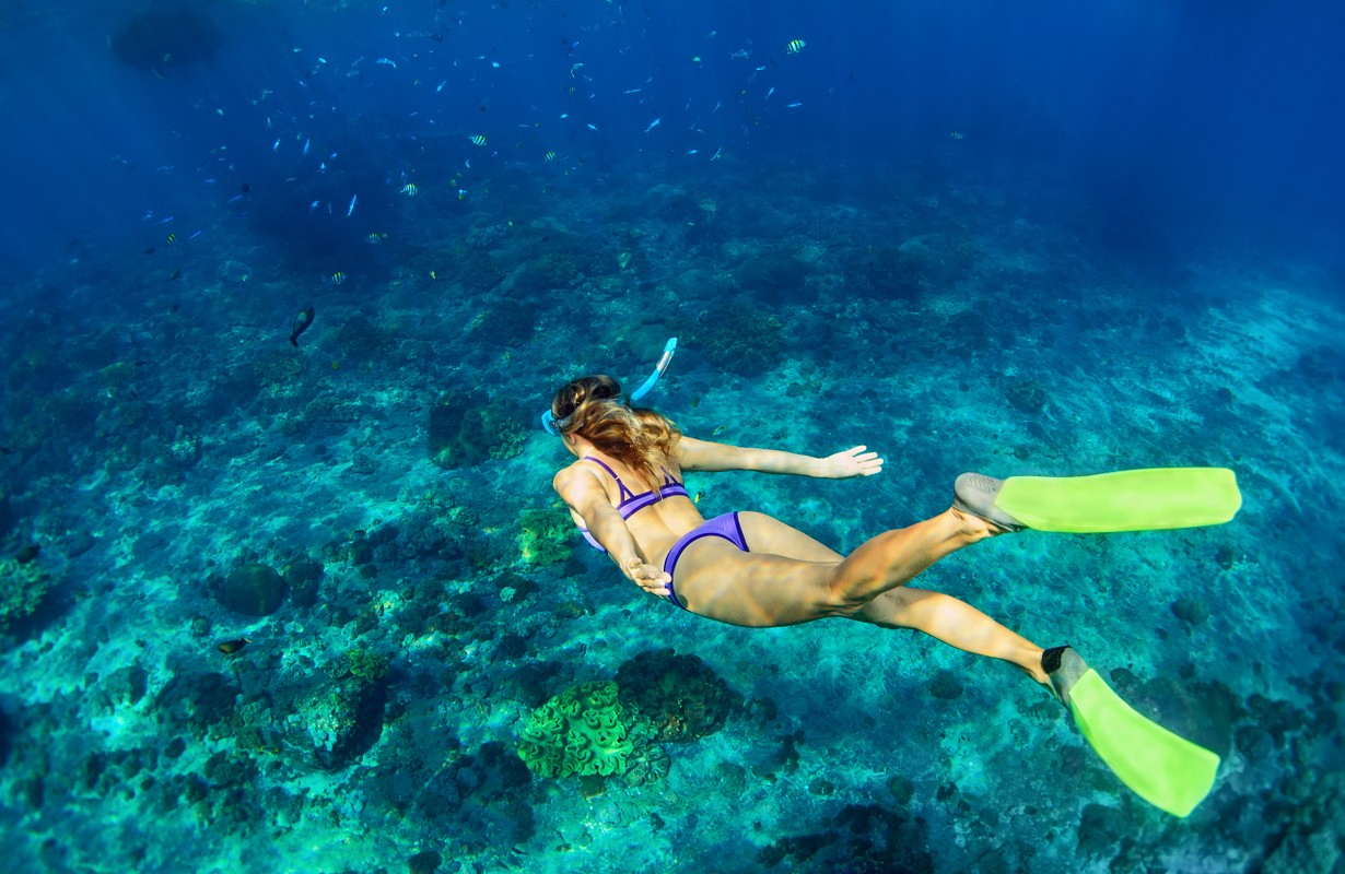 Girl in snorkeling mask dive underwater with tropical fishes in coral reef sea pool.