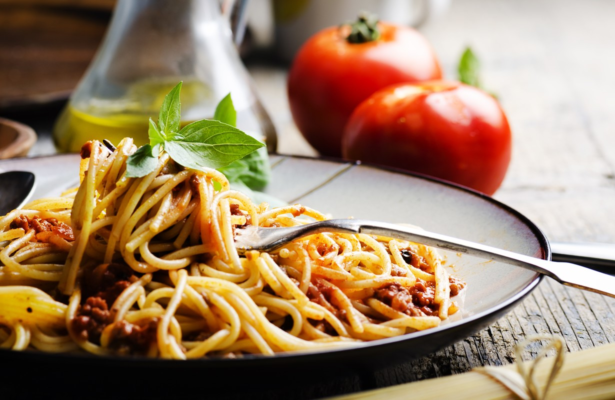 Italian spaghetti on rustic wooden table. Mediterranean cuisine with pasta ingredients- bolognese sauce, olive oil, basil and tomato.