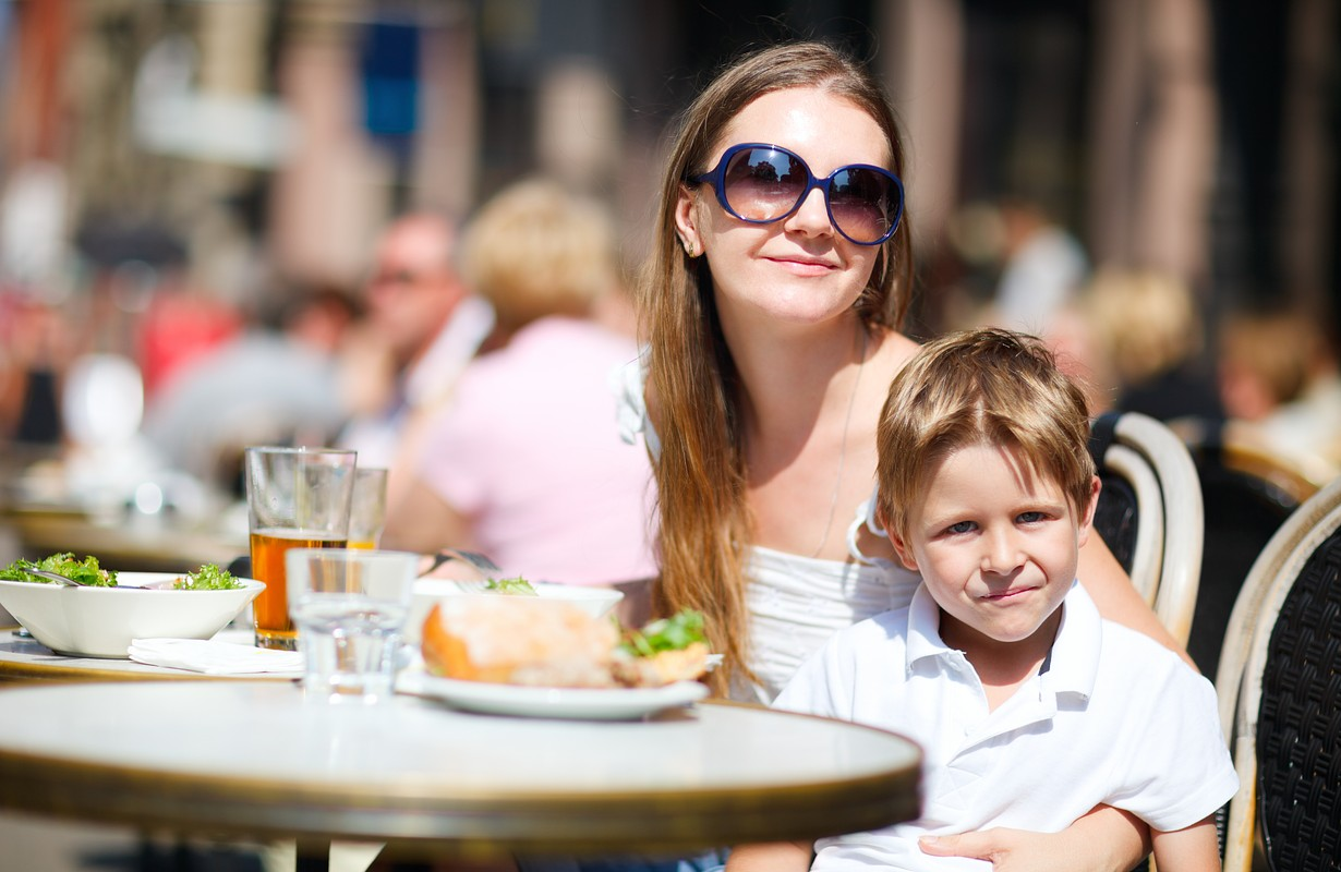 Young mother and her son having lunch in outdoor restaurant