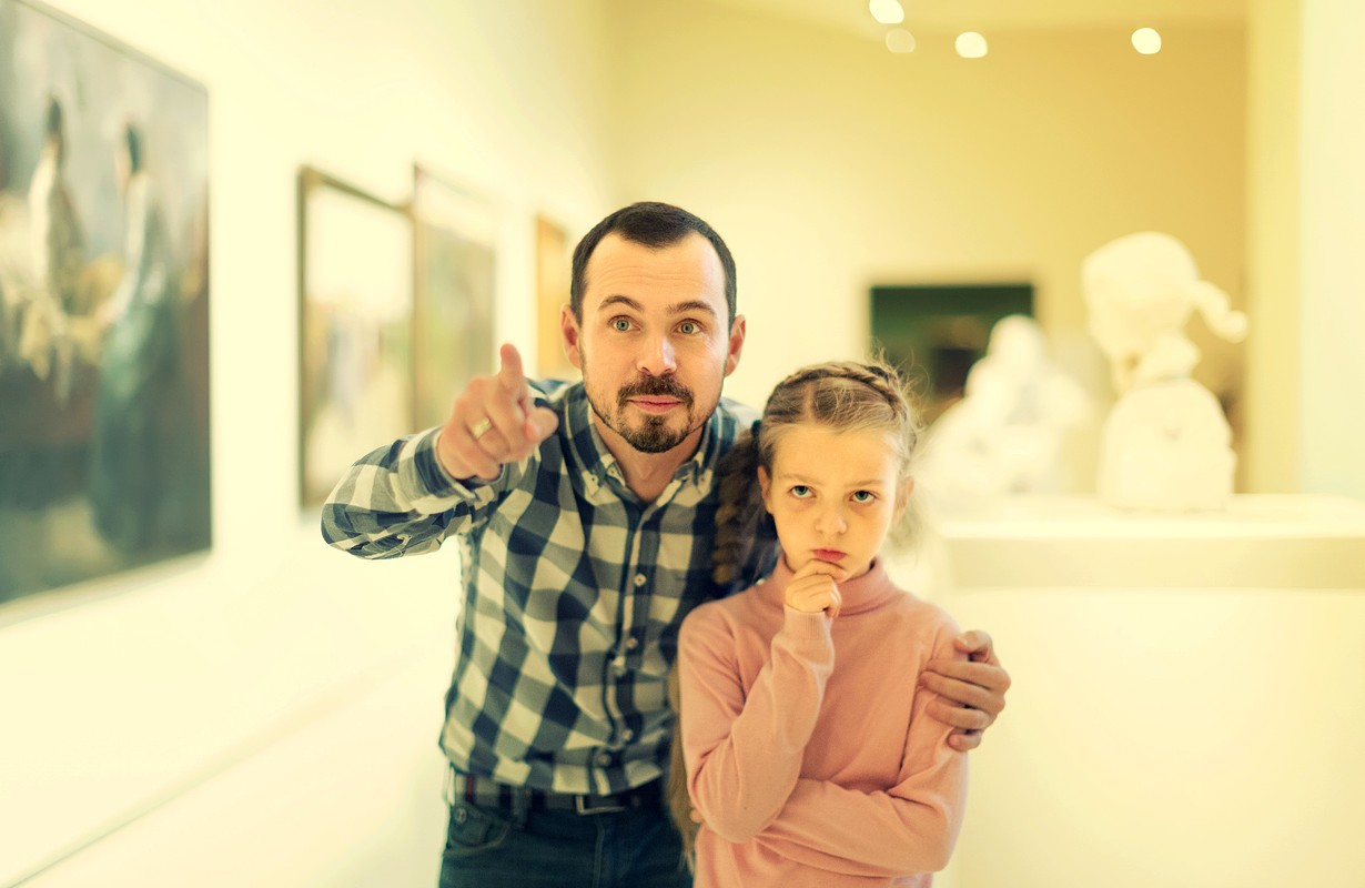 Father and daughter regarding paintings in halls of museum