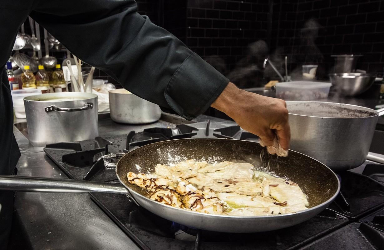 Italian chef preparing steaks in restaurant.