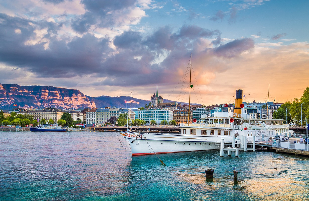 Panoramic view of the historic city center of Geneva with traditional paddle steamer boat on Lake Geneva in beautiful golden evening light at sunset with blue sky and clouds in summer, Switzerland