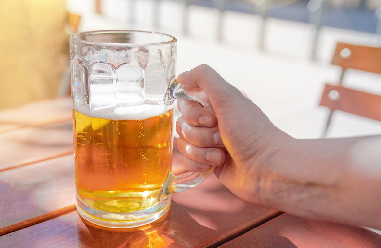 outdoor shot of hand of a woman holding large mug of beer on beer garden table on sunny day