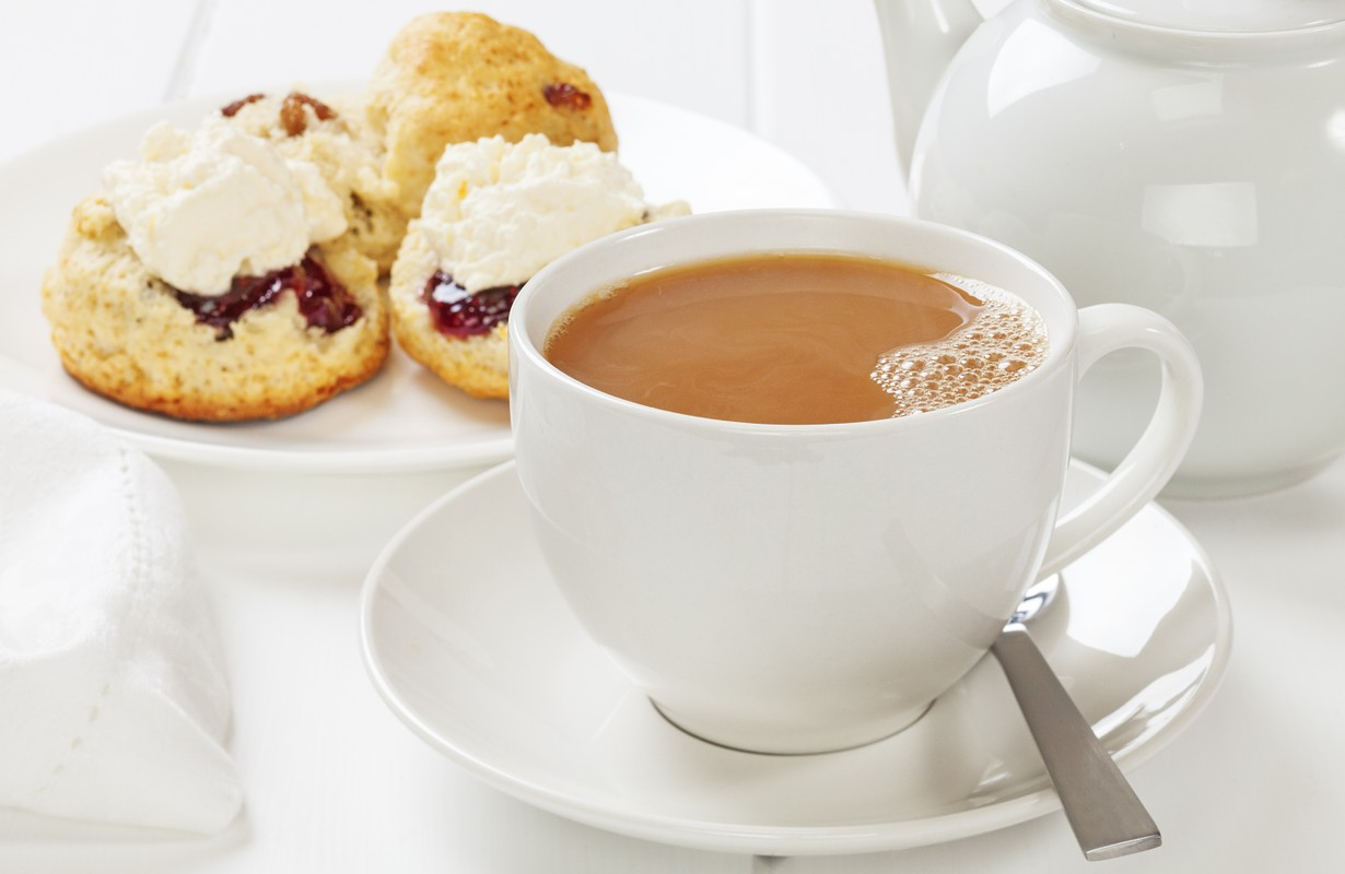 A cup of tea with scones, jam and cream.
