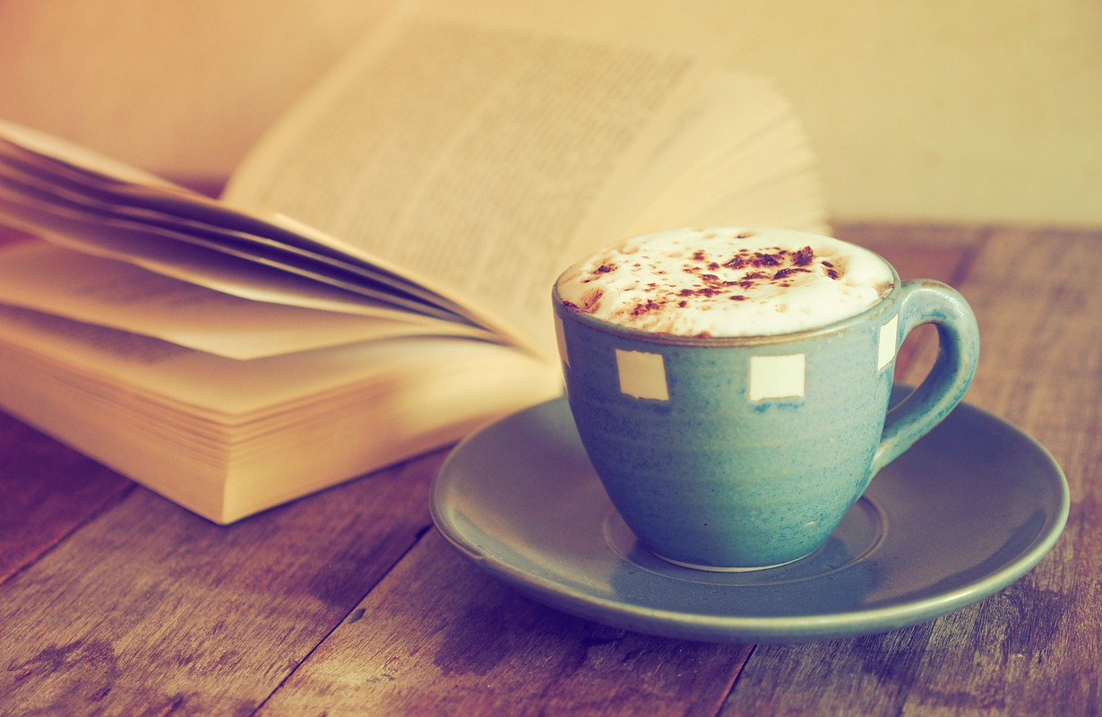 cup of coffee with book in coffee shop vintage color
