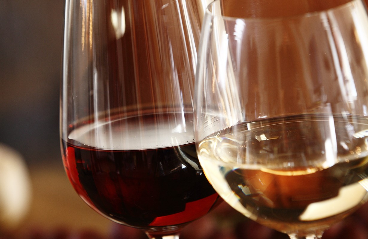 Elegant glasses of red and white wine served together on a dining table for a formal meal, close up of the bowls of the wineglasses and the wine