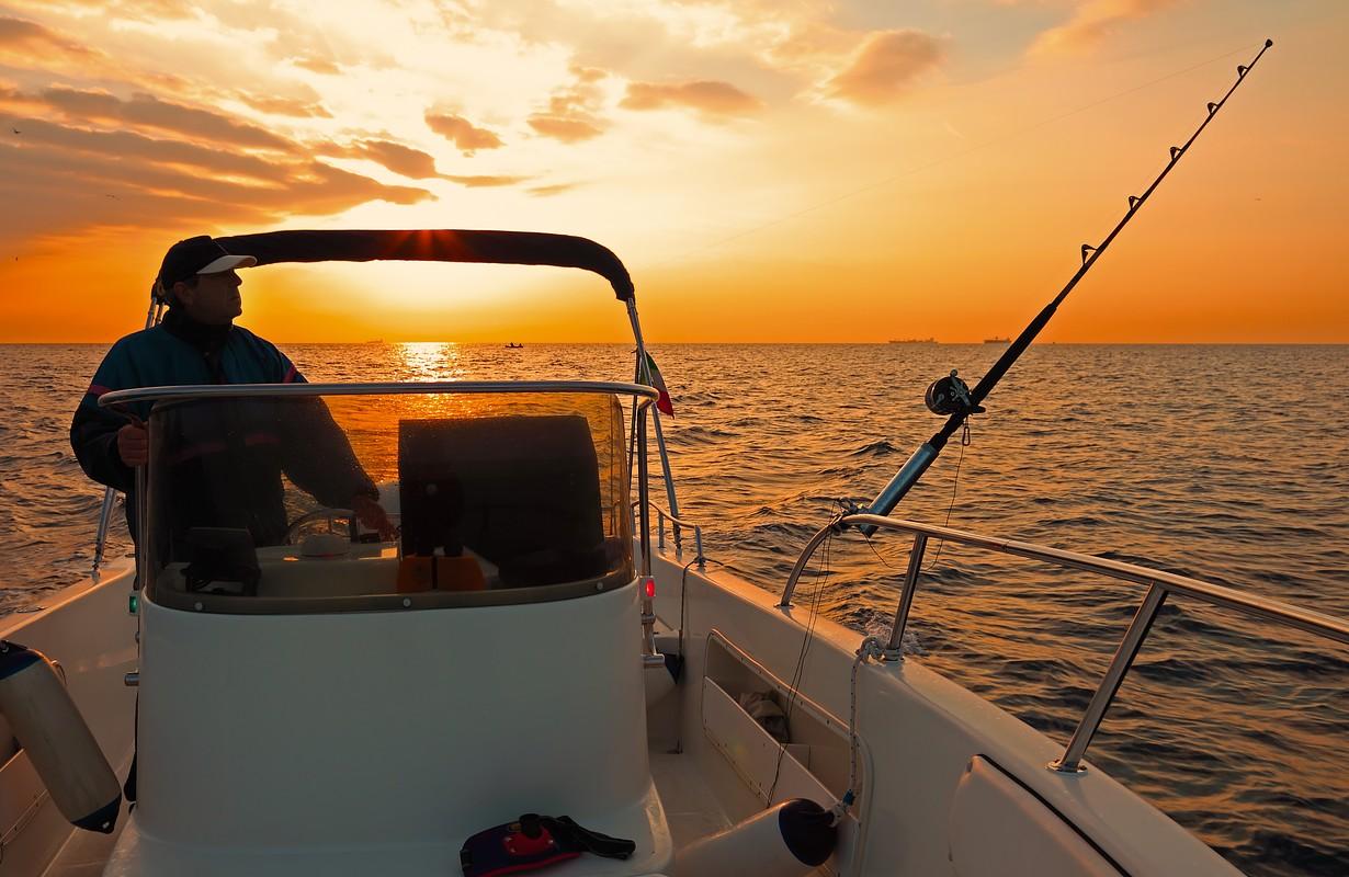 Fishing boat and fisherman in ocean at dawn
