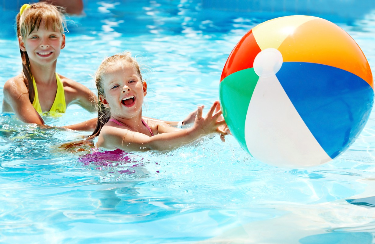 Children playing with a ball in a swimming pool.