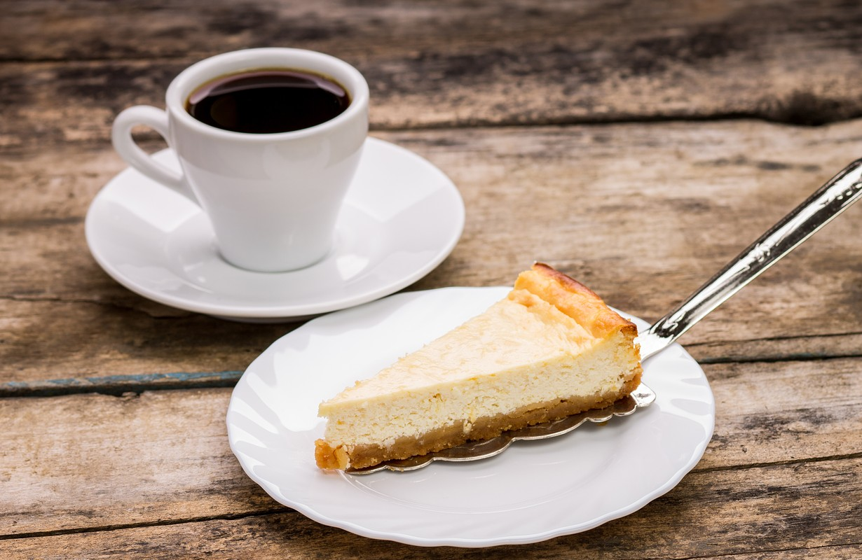 cup of coffee with slice of cheesecake on wooden background