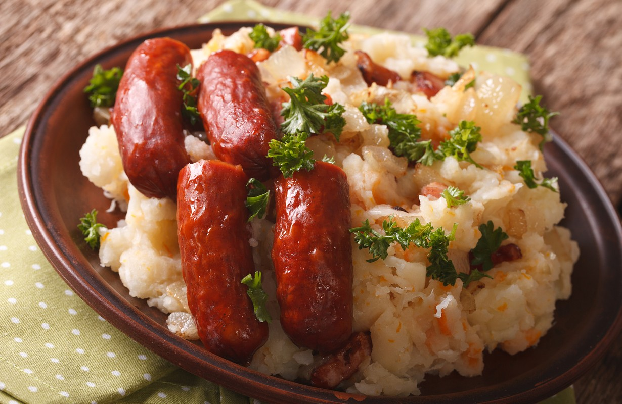 stamppot mashed potatoes, cabbage and carrots, with sausages close-up on a plate. Horizontal