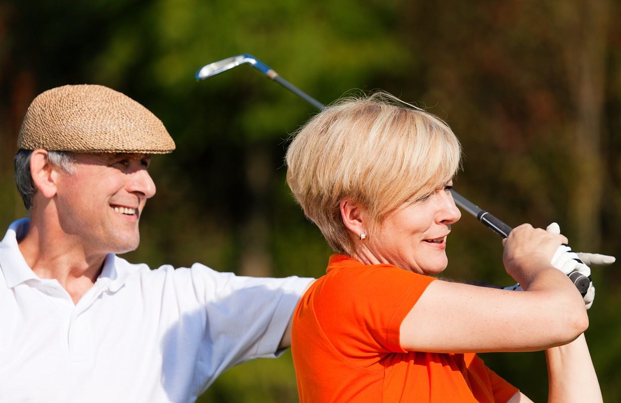 senior couple playing golf on a summer afternoon,