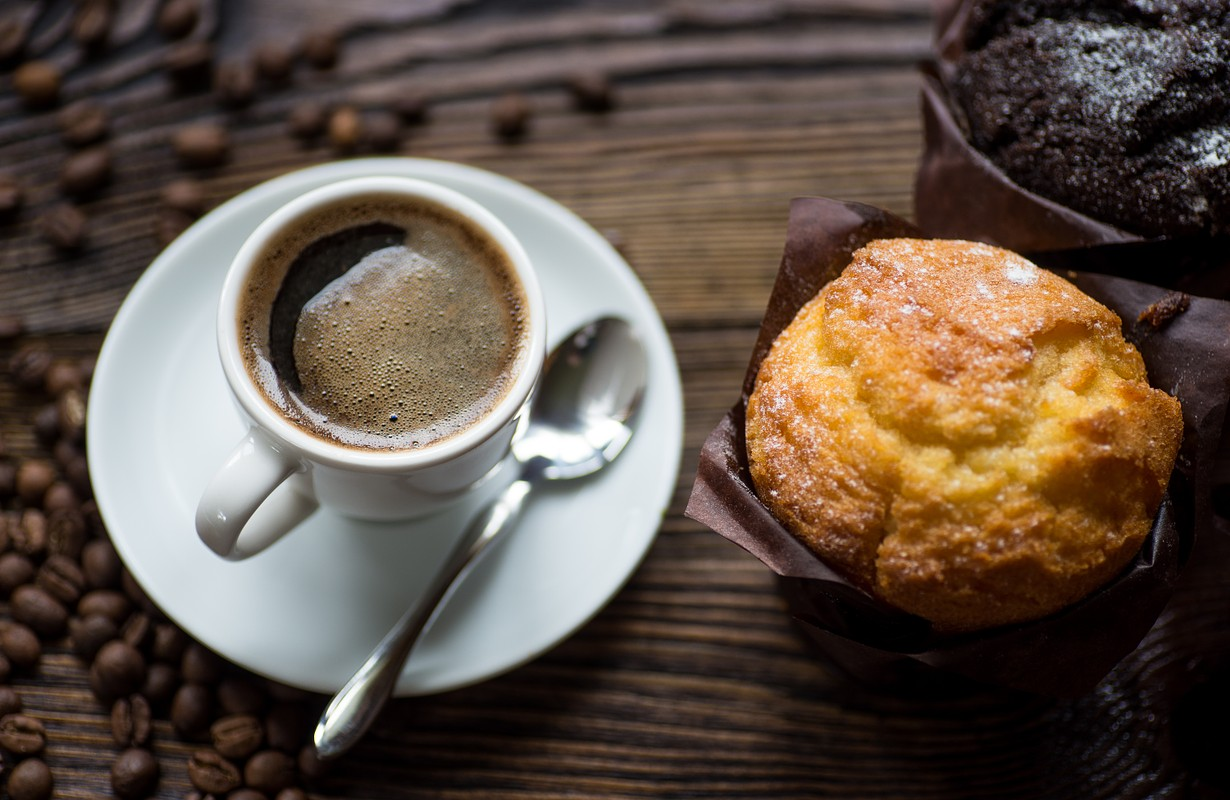 Classic style espresso shot with chip muffin and coffee beans on old wooden table. Top view.
