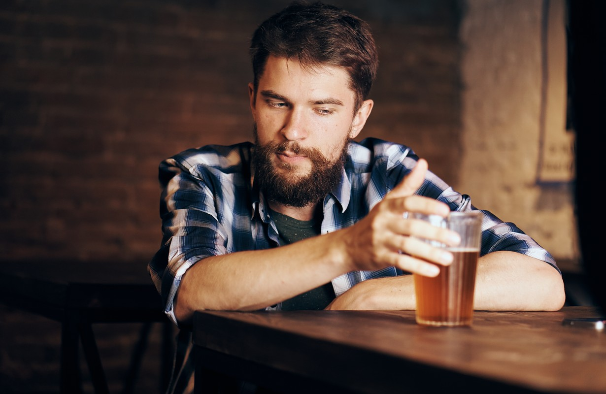 Man with a beard with a glass of beer in a bar
