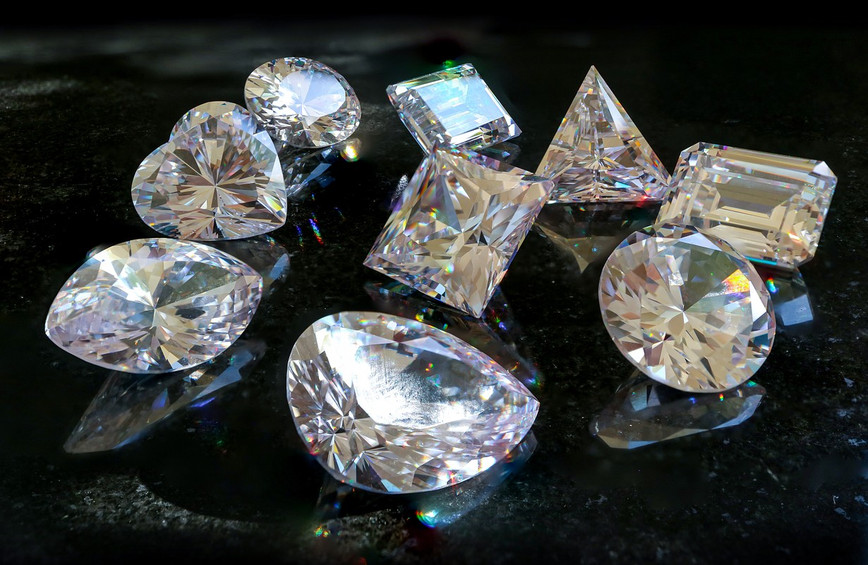 All shapes and cuts of diamonds, princess, cushion, heart, pear, marquise, radiant, Asscher, emerald and oval. Scattered diamonds laid out on black marble.
