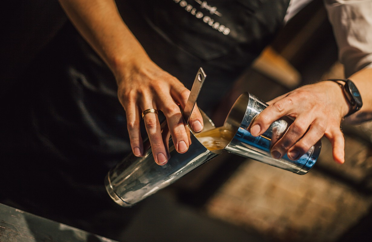 Bartender making alcoholic cocktail, summer cocktail in bar