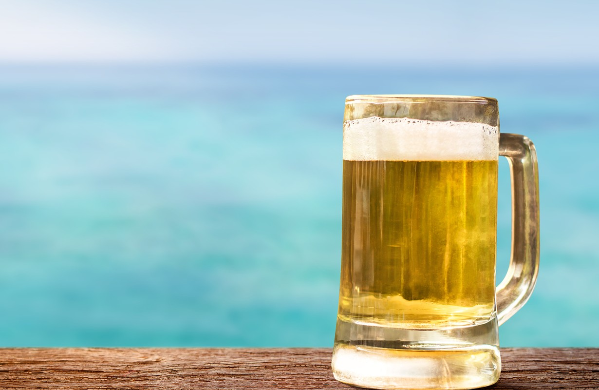 Glass of Beer on Wooden Table in front of the Sea