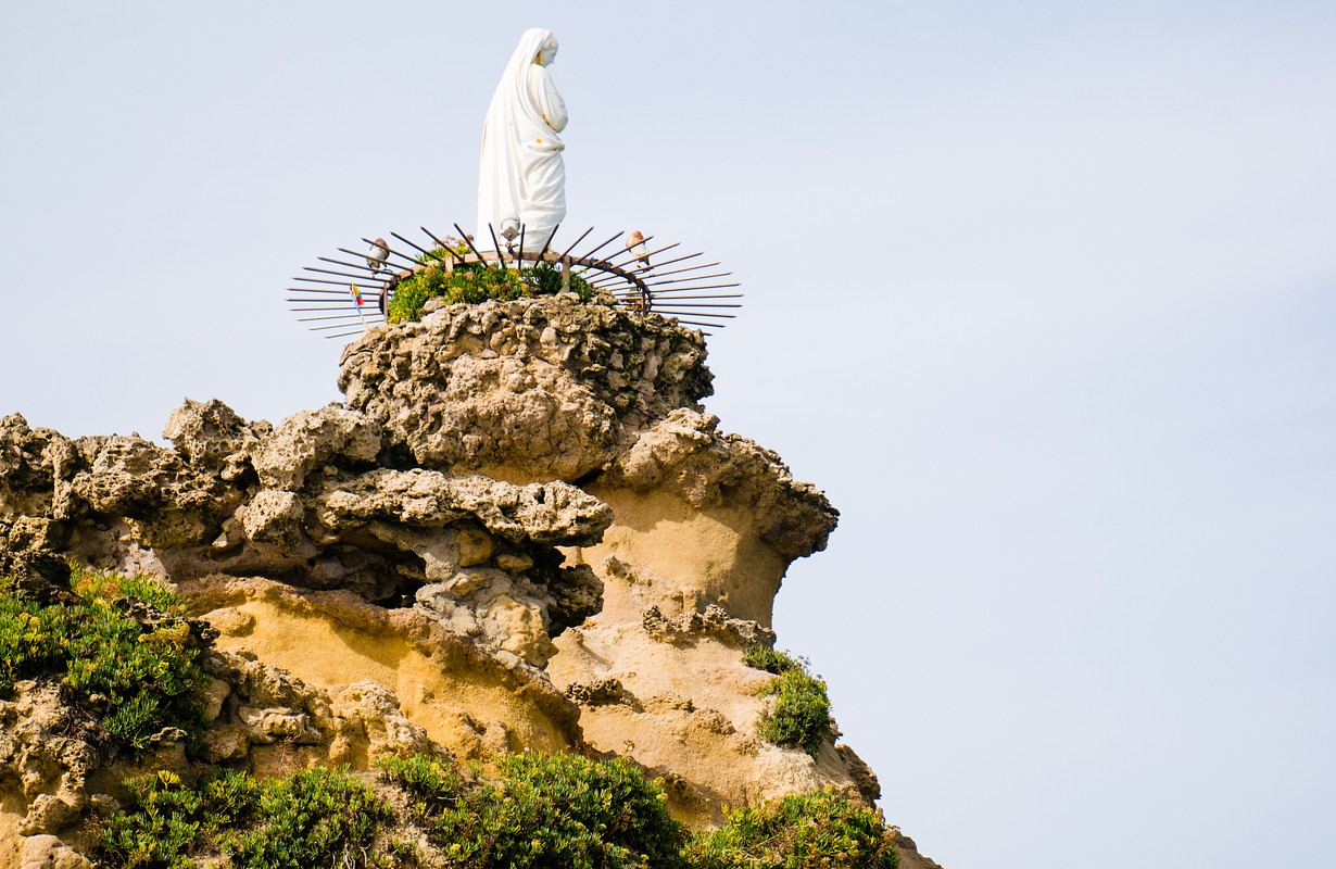 The statue of the Virgin Mary sits atop the rock formation at Rocher de la Vierge, Biarrtiz, Basque Country