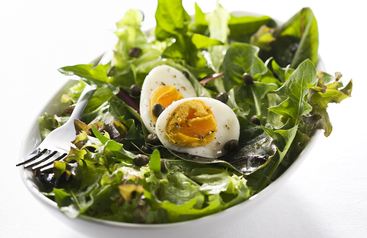 Fresh mixed green salad with egg close up
