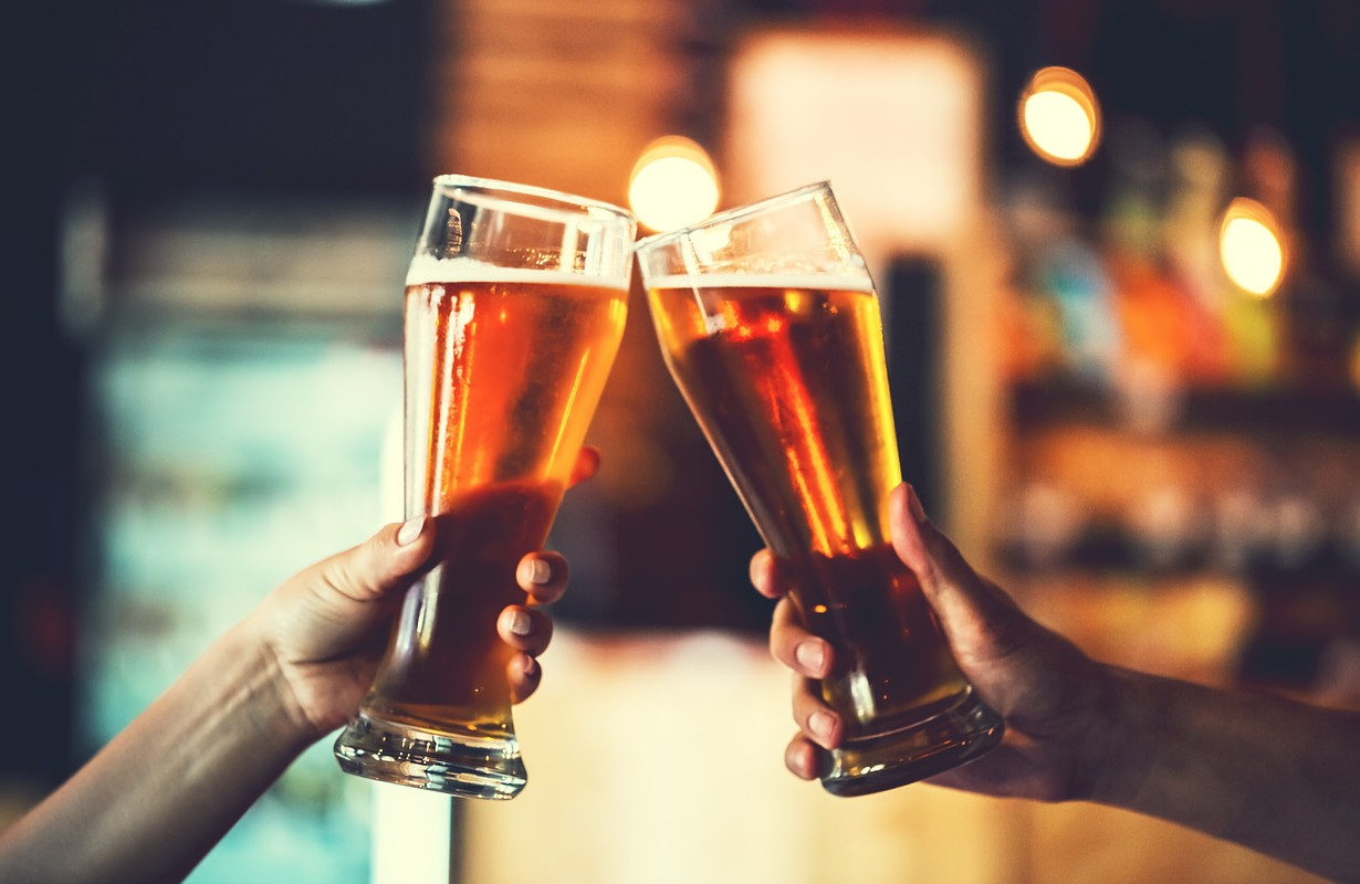 Two friends toasting with glasses of light beer at the pub