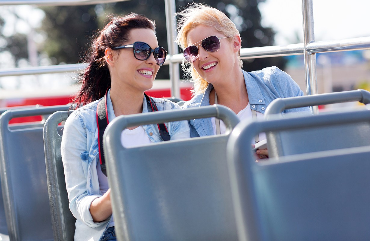 two cheerful tourists enjoying open top bus tour in the city