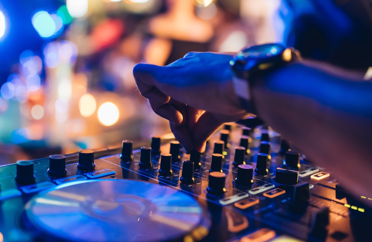DJ plays live set and mixing music on turntable console at stage in the night club. Disc Jokey Hands on a sound mixer station at club party. DJ mixer controller panel for playing music and partying