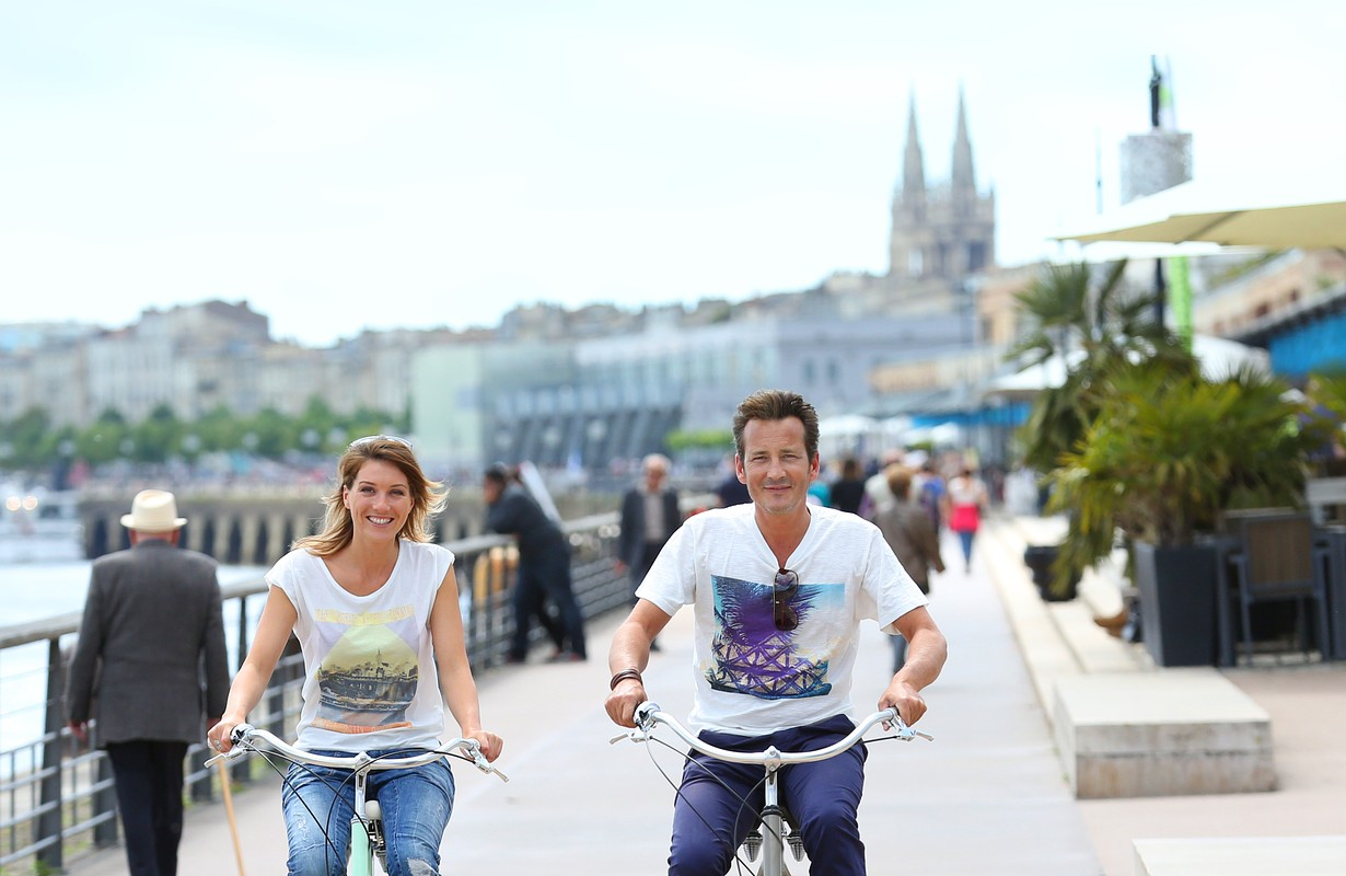 Cheerful couple riding bikes in Bordeaux