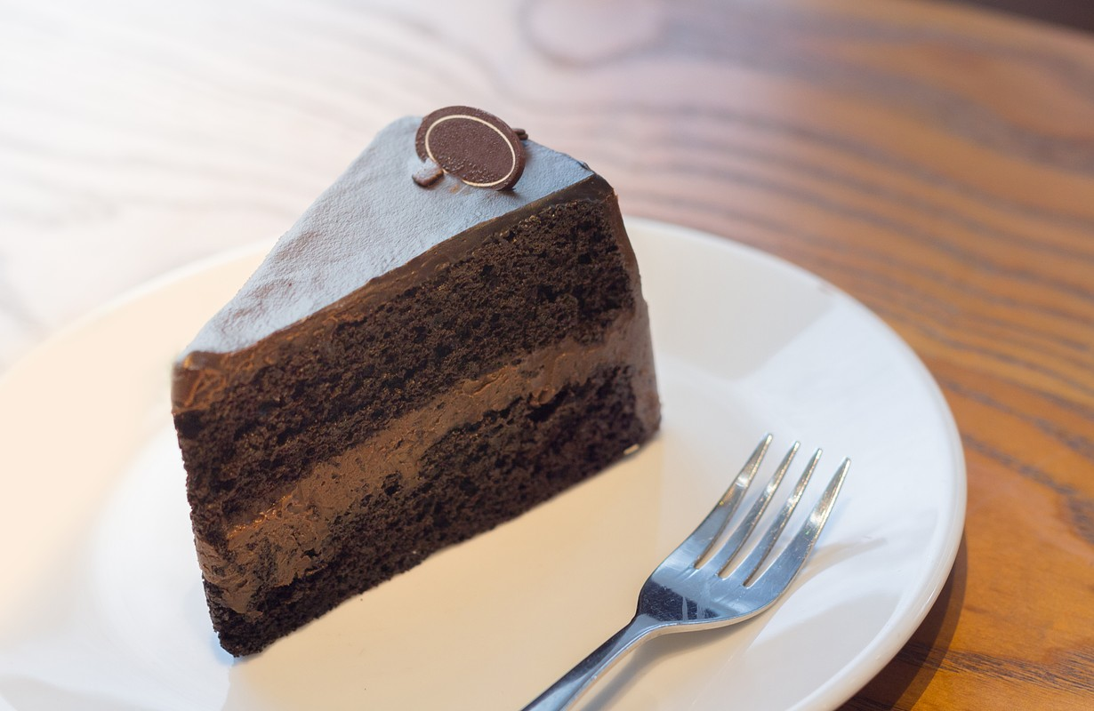 Dark chocolate cake on dish and wood table