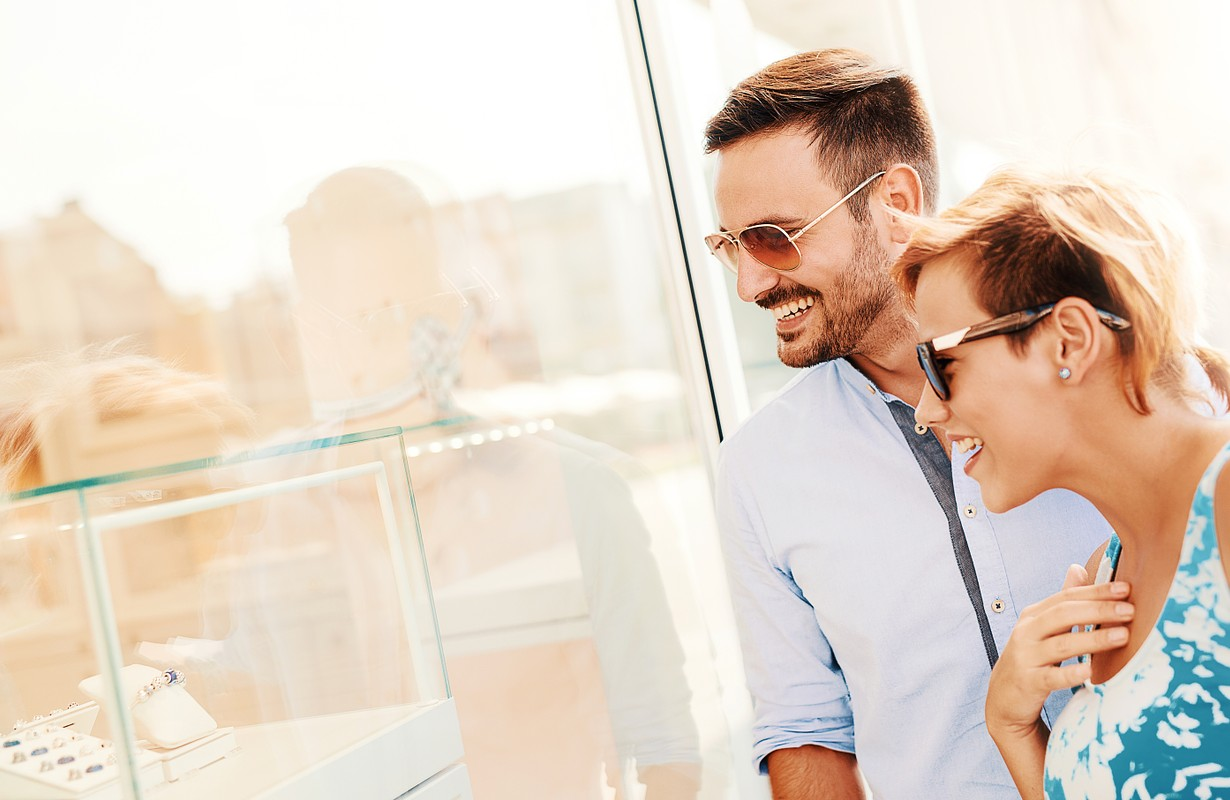 Young couple looking through a store window and enjoying together in shopping. Consumerism, shopping and lifestyle concept