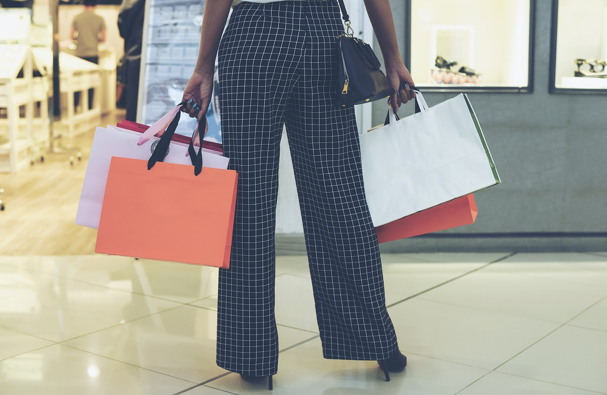Midsection of woman walking with shopping bags in the blurred shopping mall department store background