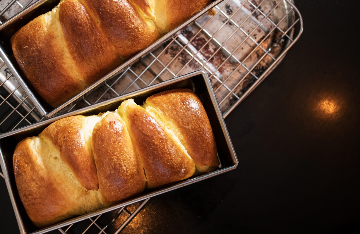Fresh brioche bread on black table top with copy space. Top view. - Picture