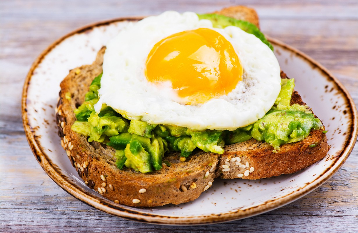 Avocado egg sandwich with whole grain bread on wooden background