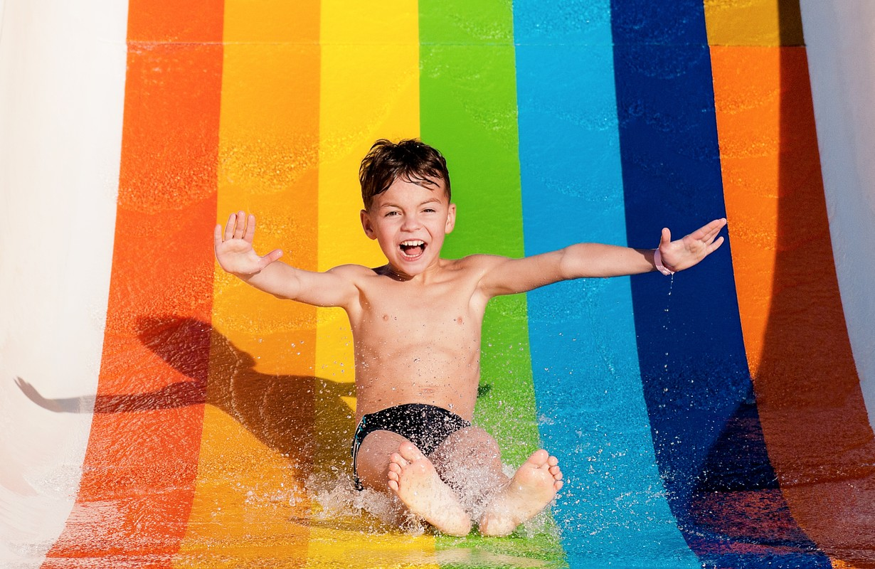 Boy has into pool after going down water slide during summer