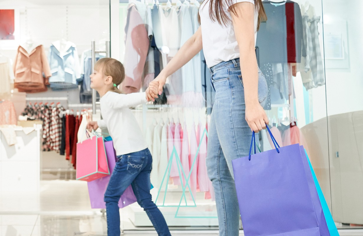 Positive girl keeping hand of woman and running in shops
