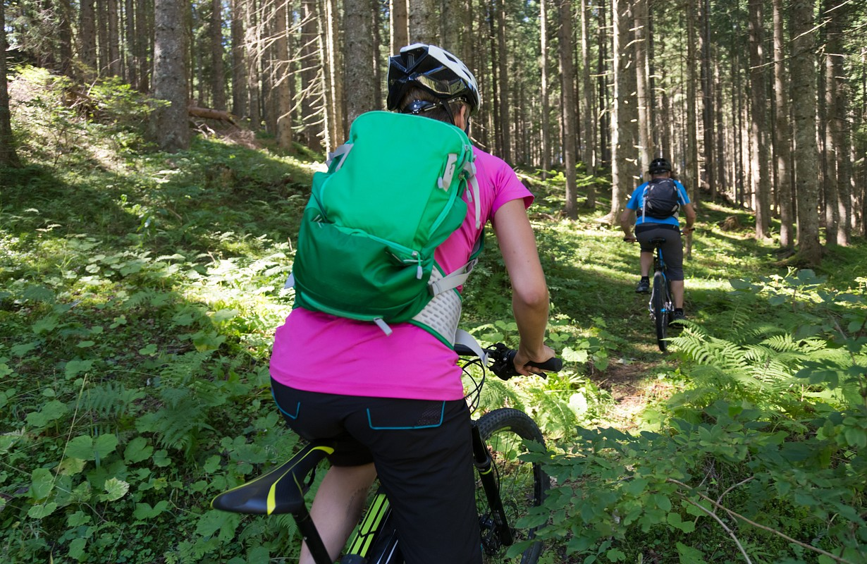 Active sporty couple riding mountain bikes on demanding forest trail