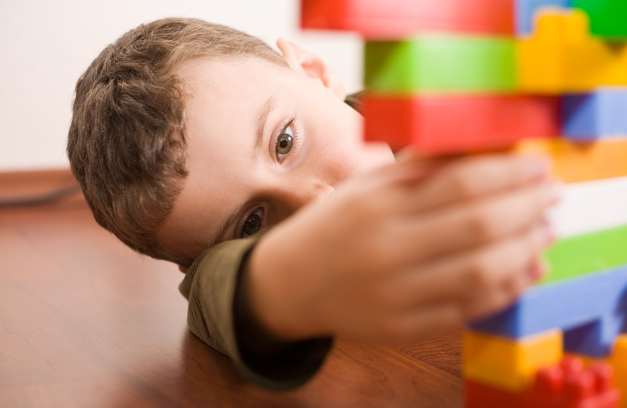 8 year old boy playing with colorful cubes on the floor