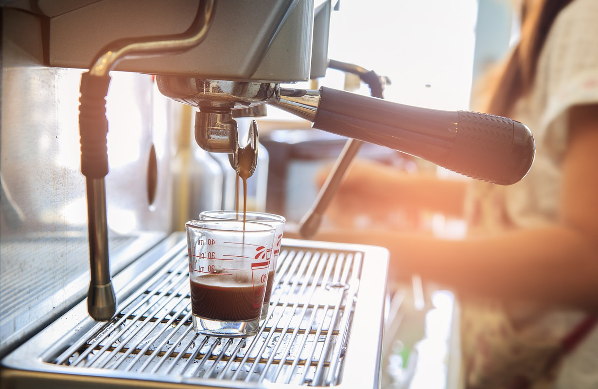 Close-up of espresso pouring to cup from coffee machine. Small business food and beverages