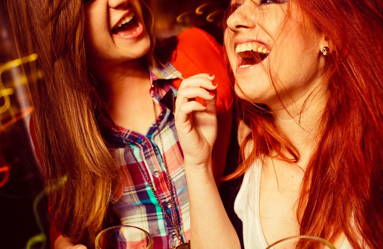Girls having fun and drinking beer in night club