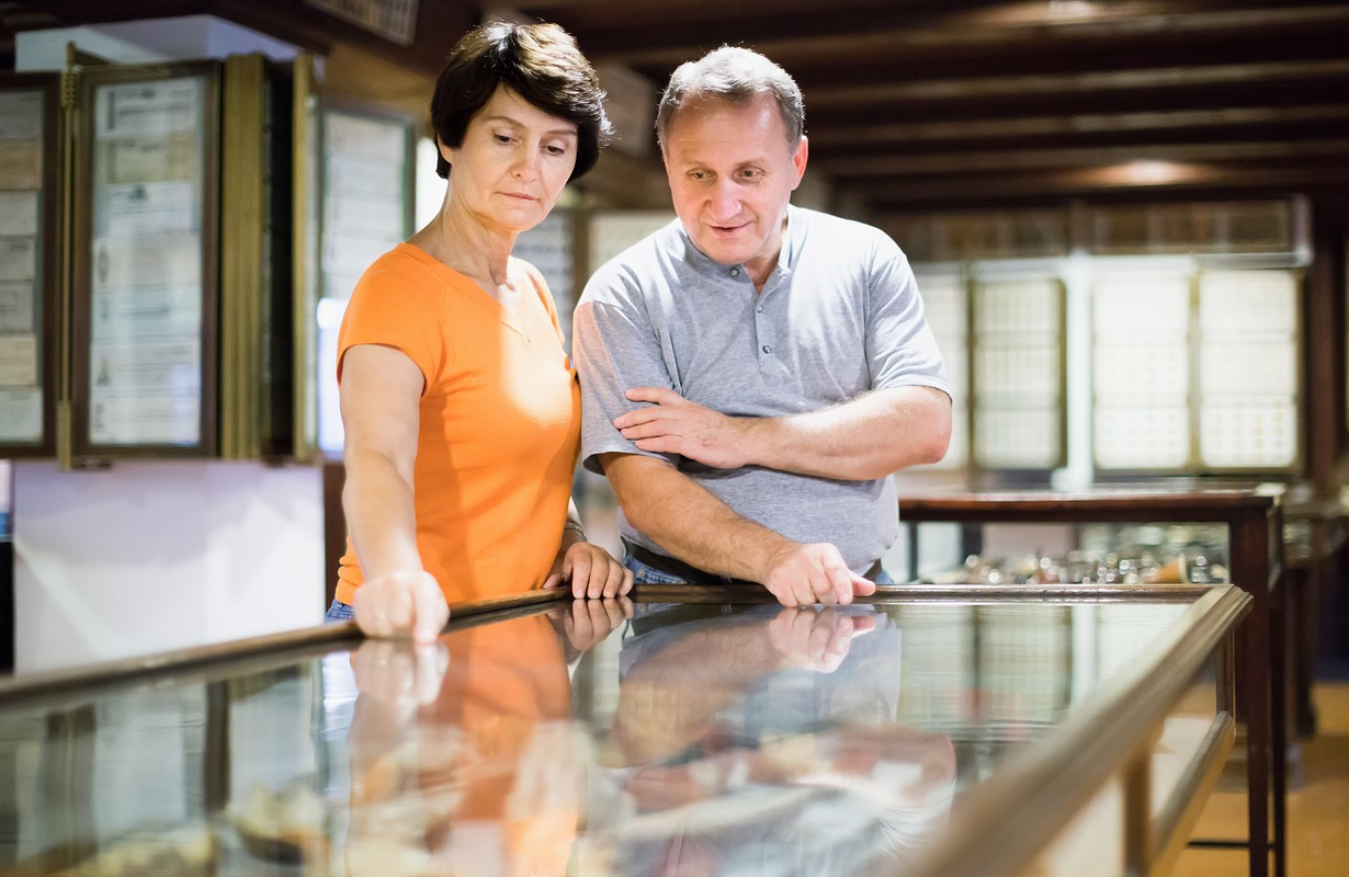 Couple is looking at the exposition under glass in historical museum