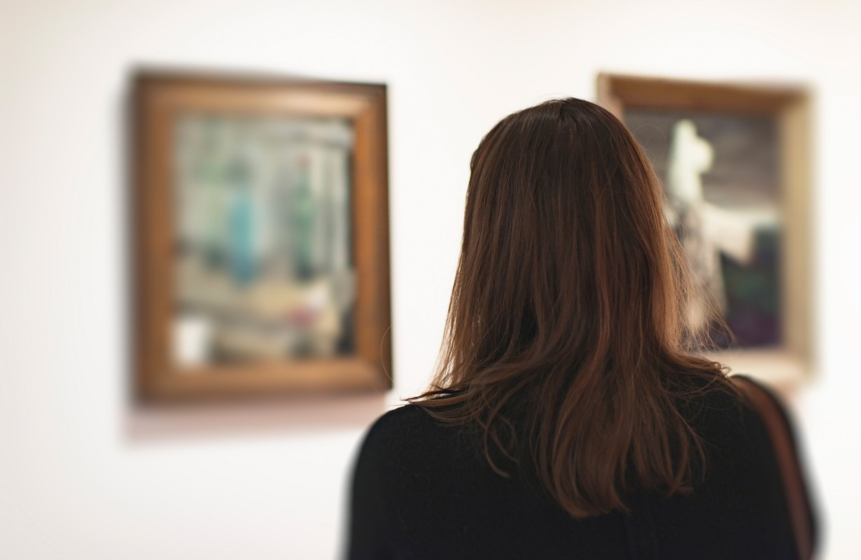 Brunette woman looking at artwork in museum. Rear view.