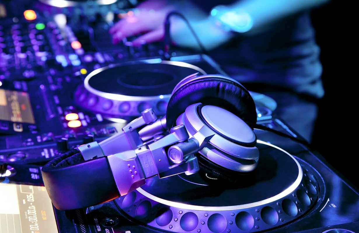 Dj playing the track in the nightclub at a party. DJ headphones
