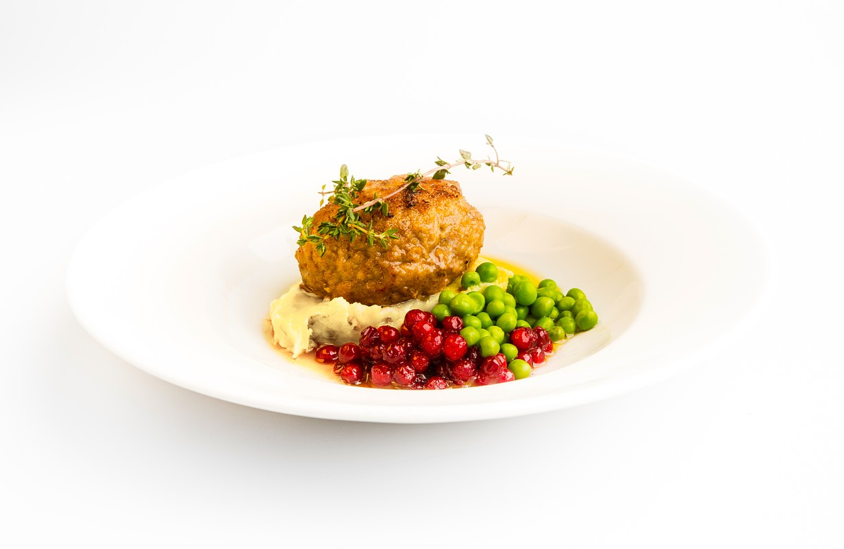 A side angle photograph against a black background of a Swedish dinner or lunch recipe, Wallenbergare. consisting of a fried, succulent veal patty, green peas, lingonberries and mashed potatoes.