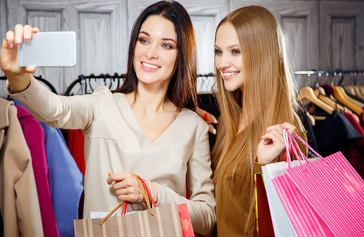 Pleasant contented young girls shopping in a mall and making selfie while holding packages
